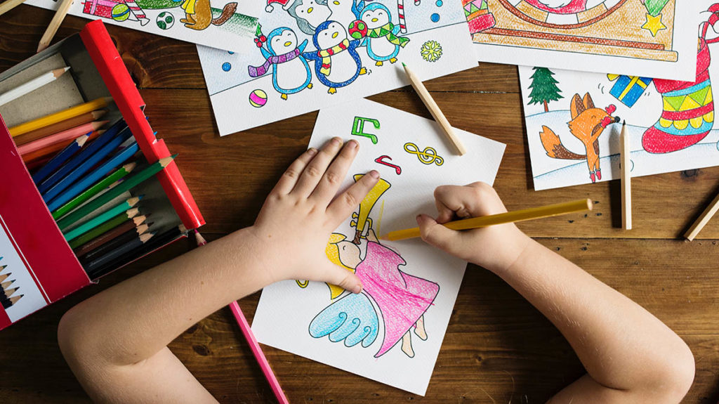 Child's hands coloring on wooden table